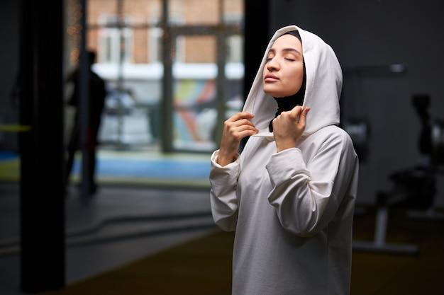 Мусульманская женщина в хиджабе расслабляется после тяжелой тренировки в тренажерном зале в одиночестве, позирует с закрытыми глазами.