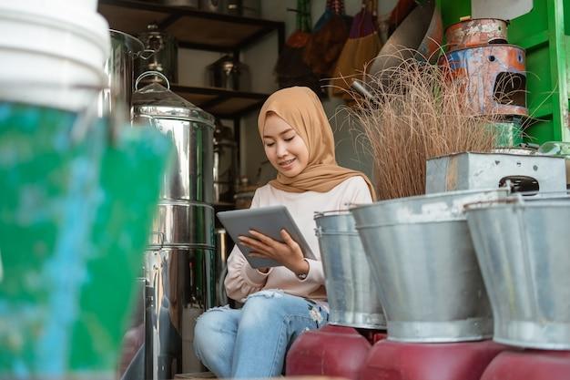Владелец магазина-мусульманки смотрит на экран планшета во время использования планшета в магазине