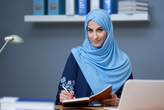 Muslim female student learning in library