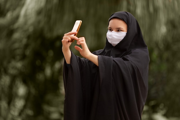 彼女のスマートフォンcovid19コロナウイルスで自分撮りをしているサージカルマスクを身に着けているイスラム教徒の女性