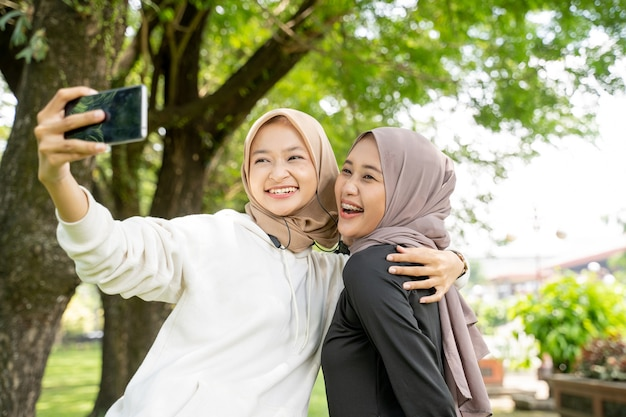 スポーツ中にスマートフォンを使用して屋外で自分撮りやビデオ通話をしているイスラム教徒の友人