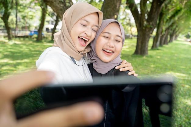 Muslim friend taking selfie or video calling outdoor using her smart phone during sport