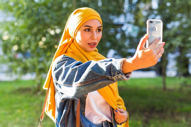 Muslim girl in hijab makes a selfie on the phone standing on the street of the city