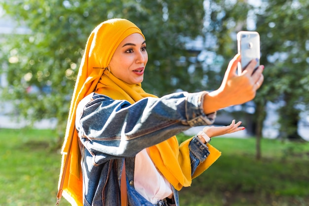 Muslim girl in hijab makes a selfie on the phone standing on the street of the city.