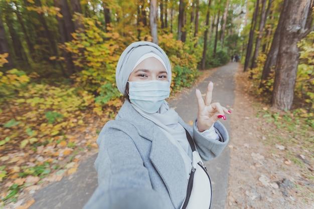 의료용 마스크를 쓴 이슬람 소녀가 공원에서 이슬람 아라비아 여학생의 셀카 초상화를 만든다