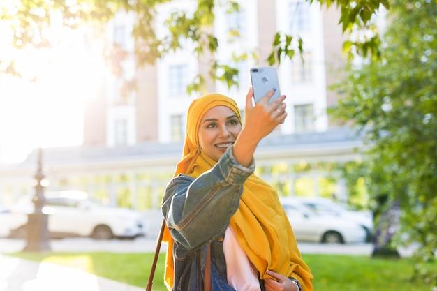 ヒジャーブのイスラム教徒の少女は、街の通りに立っている電話で自分撮りをします