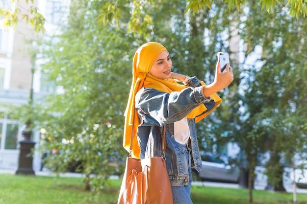 히잡의 무슬림 소녀가 도시의 거리에 서있는 전화로 셀카를 만듭니다.