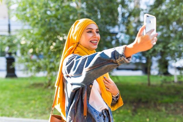 ヒジャーブのイスラム教徒の少女は、街の通りに立っている電話で自分撮りをします。