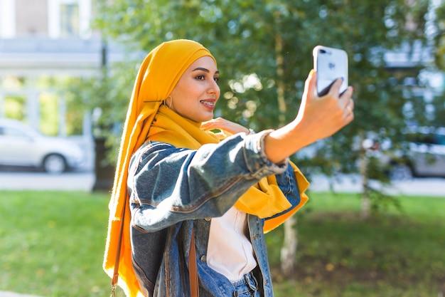 히잡의 무슬림 소녀가 도시의 거리에 서있는 스마트 폰으로 셀카를 만듭니다.
