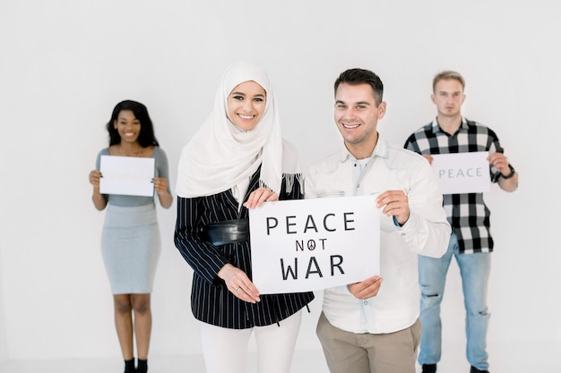Мусульманская девушка в белом хиджабе и кавказский мужчина улыбаются, держа плакат с надписью «мира нет войны