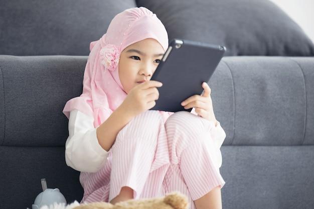 Девушка-мусульманка смотрит видео онлайн через интернет на планшете в гостиной утром