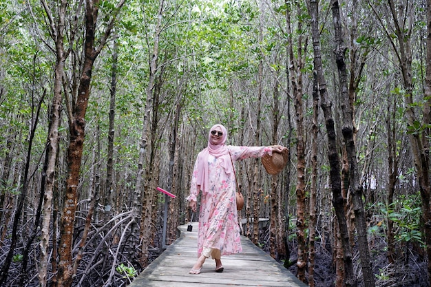 Muslim girl smiling to camera enjoy vacation at tropical sea. teenager girl wearing sun straw hat and white dress standing on wooden bridge with mangrove forest green plant background.