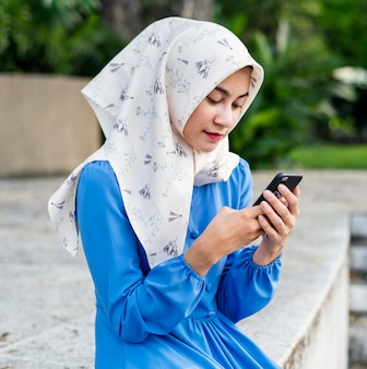 Muslim girl using a smartphone in the park