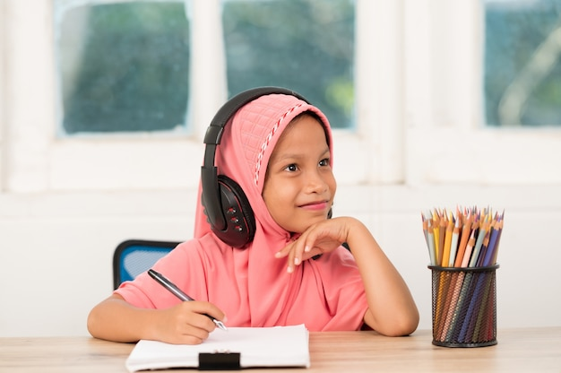 Muslim girls studying online at home to reduce social distance and prevent communicable diseases Premium Photo