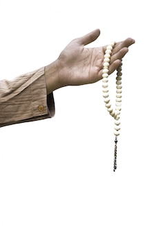 Muslim hand holding prayer beads