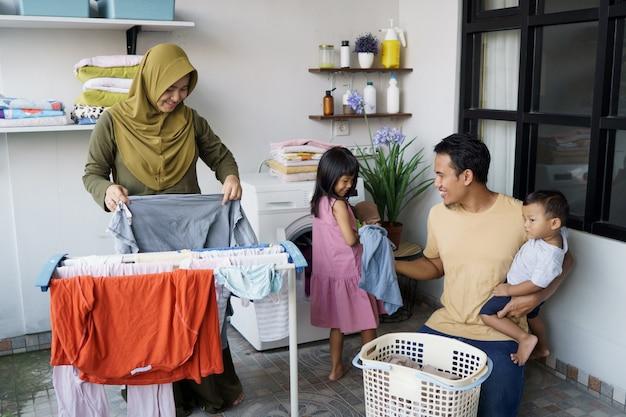 Счастливая мусульманская семья стирает дома вместе Premium Фотографии