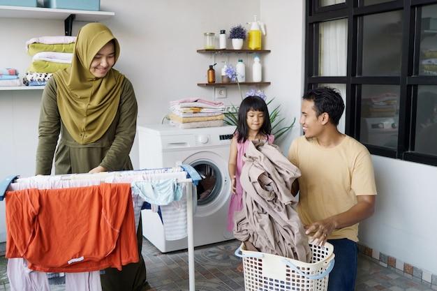 Счастливая мусульманская семья стирает дома вместе