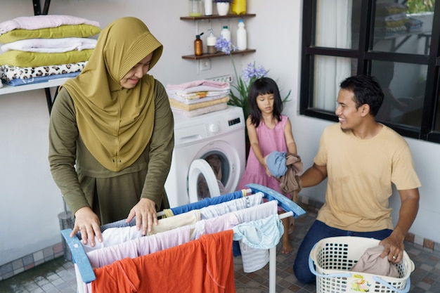 Muslim happy family doing laundry at home together
