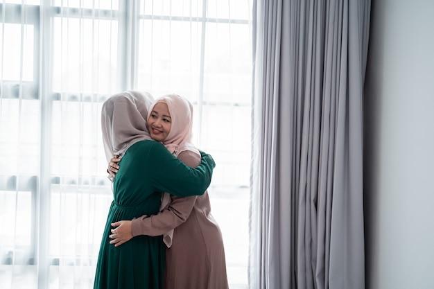 무슬림 히잡 여자는 행복하게 만나고 그녀의 자매를 안아