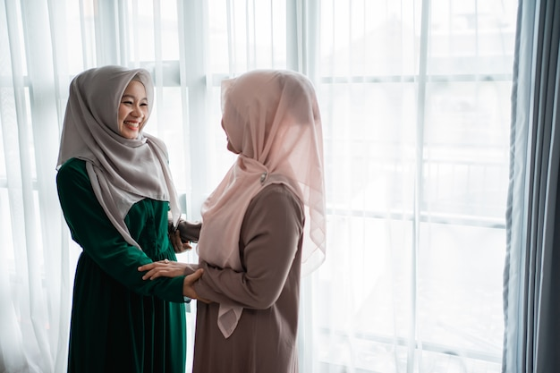 Muslim hijab woman happily meets her sister