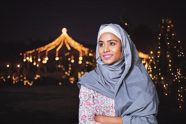 ラマダンの夜の装飾された庭の近くのイスラム教徒のインドの女性