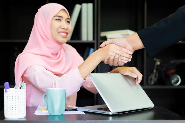 イスラム教のイスラムビジネスハンドシェイク。アジアの女性のイスラム教徒のシャツピンク。ビジネスの女性は、グラフで書く紙で手します。