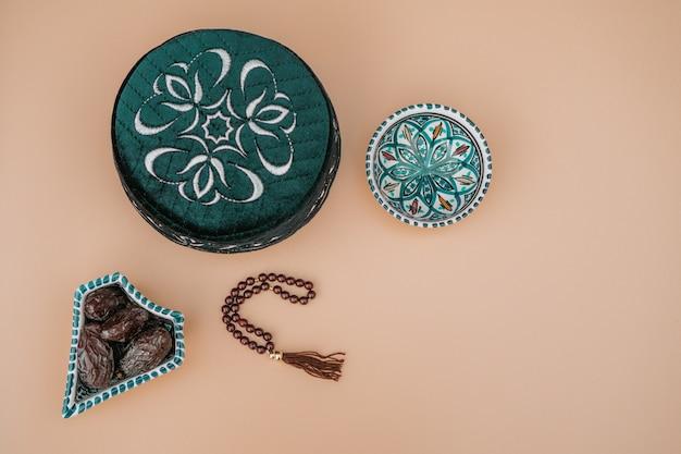 イスラム教徒のイスラム教の信仰の概念taqiyahスカルキャップ、赤いロザリオ、アラビア風のボウルに日付を記入