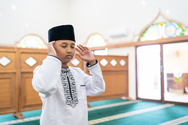 Muslim kid praying in the mosque