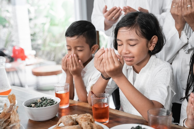 食べる前に祈るイスラム教徒の子供たち