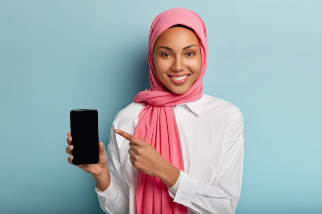 Muslim lady holds smartphone, shows blank screen to insert text or your information, wears pink hijab and white shirt