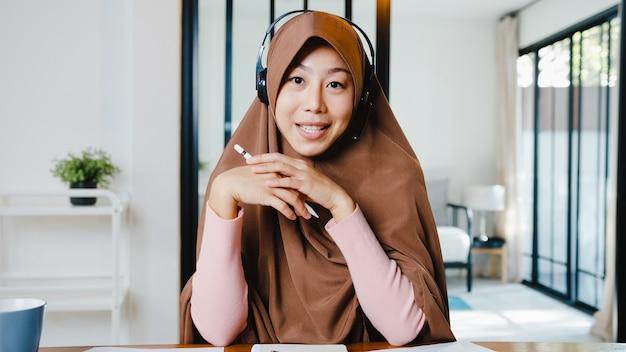 Мусульманская женщина носит наушники, используя компьютерный ноутбук, разговаривая с коллегами об отчете о продажах в видеозвонке, когда удаленно работает из дома в гостиной.