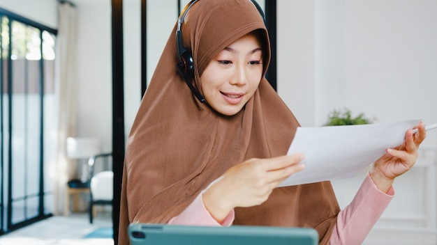 Muslim lady wear headphone using digital tablet talk to colleagues about sale report in conference video call while working from home at kitchen.