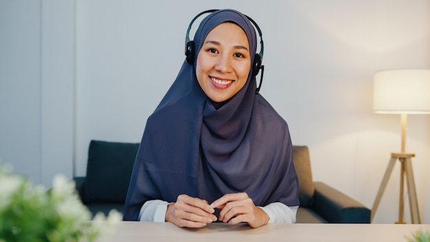 Muslim lady wear headphone using laptop talk to colleagues about sale report in conference video call while working from home office at night.