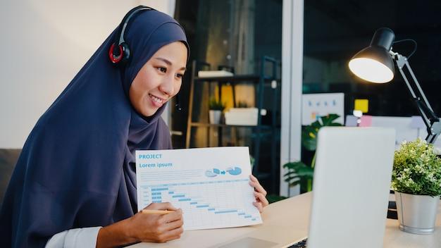 Мусульманская женщина носит наушники с ноутбуком, разговаривает с коллегами об отчете о продажах в конференц-видеосвязи, работая в ночное время из домашнего офиса.