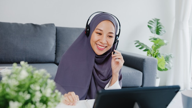 Muslim lady wear headphone using tablet talk to colleagues about sale report in conference video call while working from home at living room.