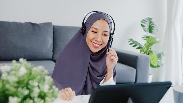 イスラム教徒の女性がタブレットを使用してヘッドフォンを着用し、自宅の居間で仕事をしているときに、会議のビデオ通話で販売レポートについて同僚に話します。