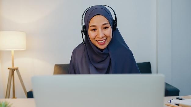 Signora musulmana indossare cuffie guardare webinar ascoltare corso online comunicare tramite videochiamata in conferenza durante la notte ufficio a casa.
