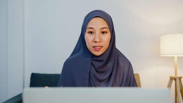 Muslim lady wear hijab using computer laptop talk to colleague about plan in video call meeting while remotely work from home night at living room.