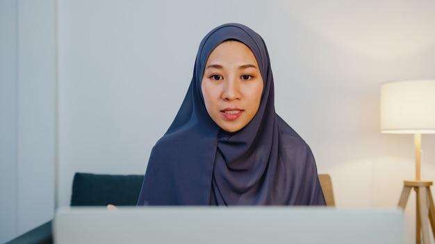 イスラム教徒の女性は、コンピューターのラップトップを使用してヒジャーブを着用し、自宅の夜から居間でリモートで作業しながら、ビデオ通話会議の計画について同僚に話します。