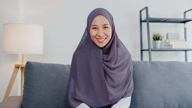 イスラム教徒の女性は、コンピューターのラップトップを使用してヒジャーブを着用し、自宅の居間でリモートで作業しながら、ビデオ通話会議の計画について同僚に話します。
