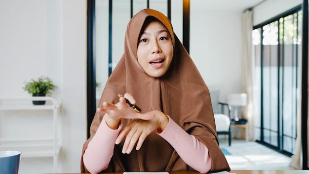 이슬람 여성은 거실에서 집에서 원격으로 작업하는 동안 화상 통화 회의 계획에 대해 동료에게 컴퓨터 랩톱을 사용하여 히잡을 착용합니다.