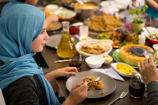 Muslim little girl having dinner at home with her family