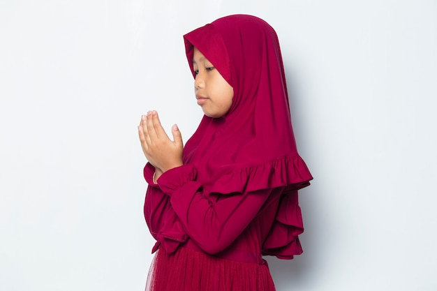 Мусульманская маленькая девочка молится, открыв руку, изолированные на белом фоне