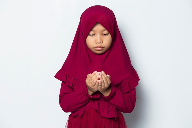 Muslim  little girl praying by open her arm isolated on white background