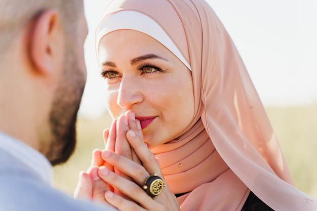 이슬람 사랑 이야기 근접 촬영. 혼합 된 커플 미소와 푸른 언덕에 포옹.