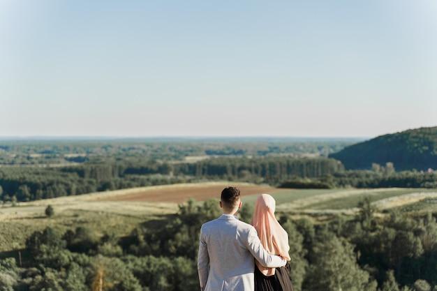 무슬림 사랑 이야기. 혼합 된 커플 미소와 푸른 언덕에 포옹.