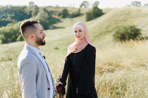 イスラム教徒の混血カップルのラブストーリー。男も女も笑顔で緑の丘を歩く。