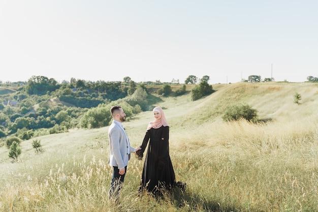혼합 커플의 이슬람 사랑 이야기. 남자와 여자는 미소를 짓고 푸른 언덕을 걷는다.