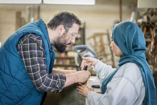Muslim male and female in workshop working together