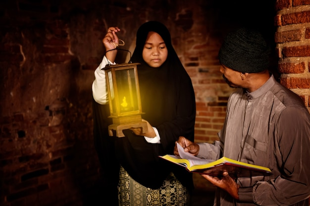 태국 아유타야의 오래된 사원에서 꾸란을 읽는 이슬람 남성과 여성